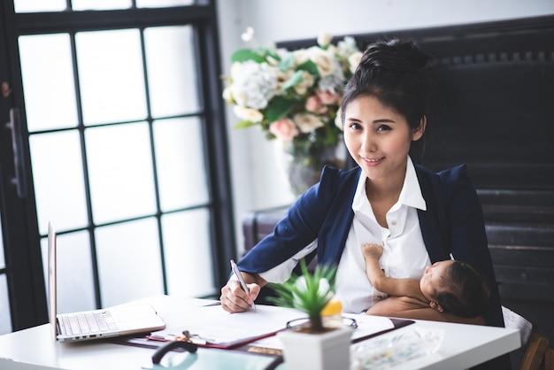忙しい若い女性が仕事やラップトップコンピューターを自宅で腕の中で彼女の赤ちゃんを押しながら研究