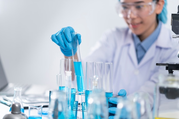 Исследователи используют стеклянную посуду и синие растворы в лабораториях