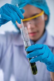 科学者は化学実験室で天然産物の抽出物、石油とバイオ燃料の溶液をテストします。
