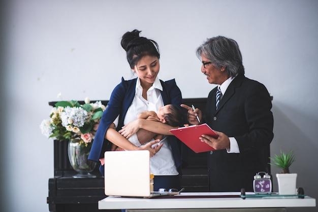 実業家は彼女の赤ちゃんを抱えることによって働いています。
