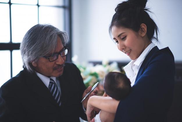 Предприниматель работает, держа ее ребенка