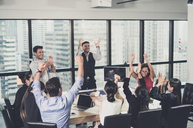 ビジネスチームが腕を組んで勝利を祝う