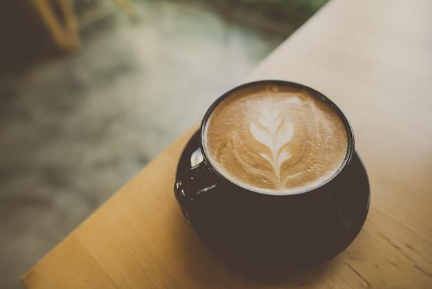 Чашка кофе латте арт на столе в кафе
