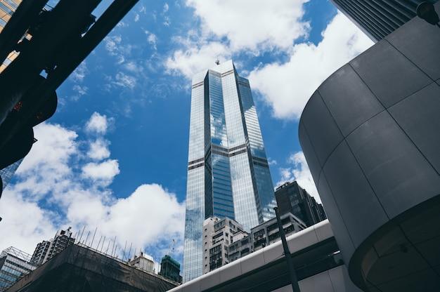 Нижний вид современных небоскребов в деловом районе против голубого неба