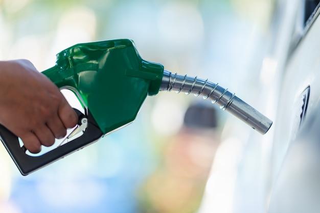 給油するガソリンポンプの燃料ポンプノズルを取り扱います。ガソリンスタンドの車両給油施設。ガソリンスタンドで白い車が燃料で満たされています。輸送および所有権の概念。