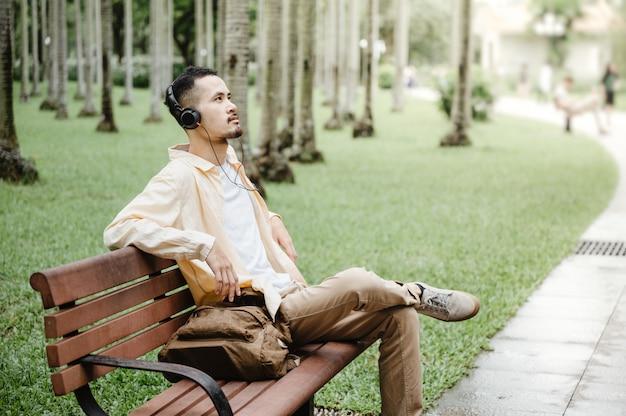 ヘッドフォンを着用し、公園でタブレットを使用する若い男恐ろしい病気の発生後のリラックスした雰囲気