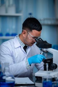 科学者は実験室で顕微鏡を使用して、医学研究