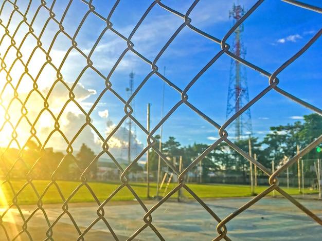 スチールフェンスケージと美しい青空と夕日