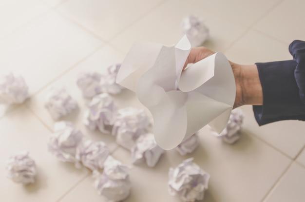 考えも失敗もコンセプト - しわくちゃの紙とゴミを持っている人間の手。