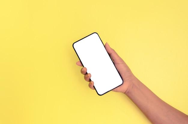 白い画面の背景を持つスマートフォンを持っている人間の手。