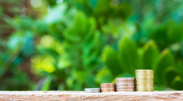 自然の背景にグラフとして配置されたコイン。ビジネスアイデア