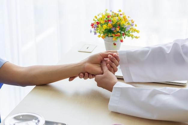 Красивый женский доктор держа руку пациента