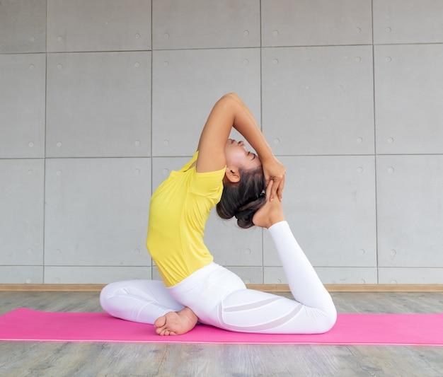 Йога спортивной одежды красивой азиатской молодой женщины нося практикуя в студии, естественном свете. концепция: йога представляет для новичка.