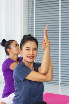 アジアのヨガの先生は、ジムで一人一人に健康的で強いことを教えます。