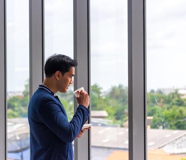 Молодой азиатский бизнесмен пьет кофе в окне офиса в удобной