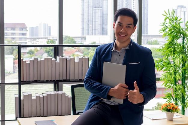 Молодой азиатский бизнесмен с ноутбуком и улыбкой в офисе