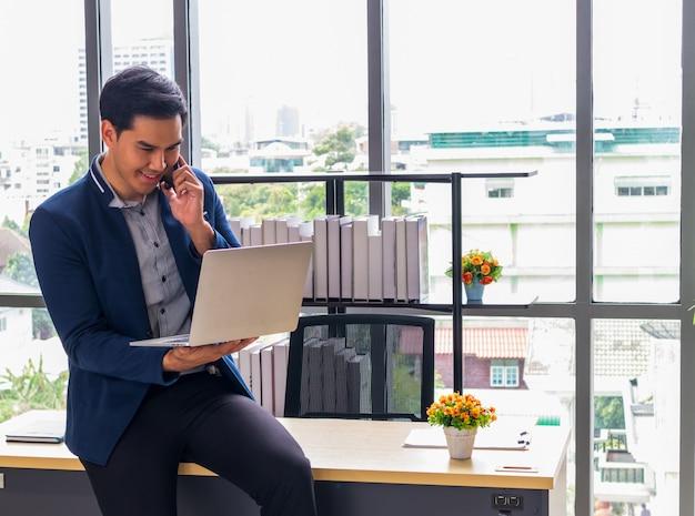 ノートブックとオフィスで笑顔で若いアジア系のビジネスマン