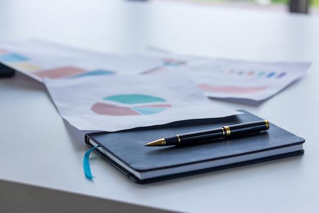 机の上のグラフ用紙で実業家の本のペン
