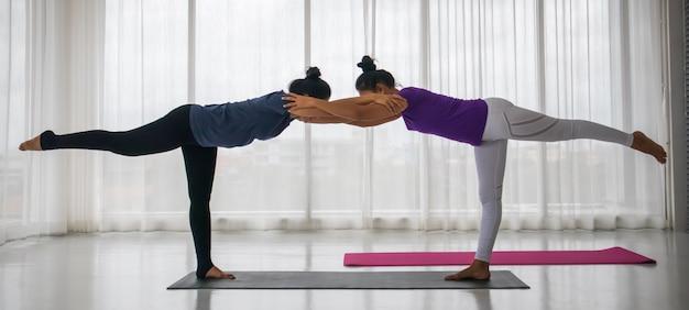 Учитель научить студента заниматься йогой концепции. азиатская женщина средних лет учит другую женщину заниматься йогой в растяжке