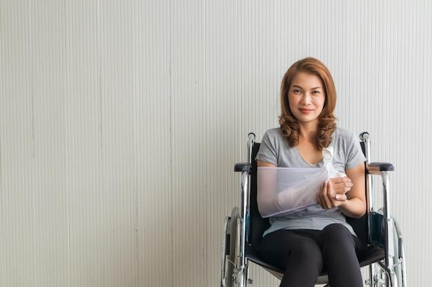 腕のスリングで骨折した腕のアジアの女性は車椅子に座って彼女の手で後援