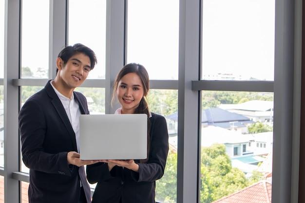 若いアジア人ビジネスマンとビジネスウーマンが一緒に仕事を相談します。職場でノートブックを見る