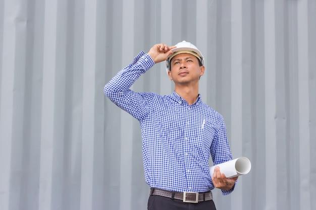 建設現場に立っている間壁に対して計画を保持しているアジアのエンジニアの肖像画