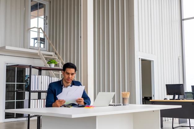 Усмехаясь бизнесмен держа документ сидя на столе, читая хорошие новости в письме, рассматривая выгодный выгодный контракт