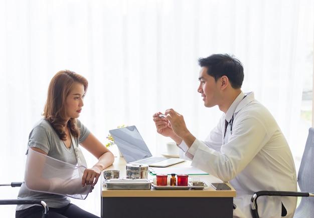 アジアの若い男性医師が骨折した患者の症状を説明しています。