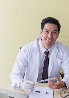 アジアの若い医者が微笑み、彼の机の上に注射器を持っていた。