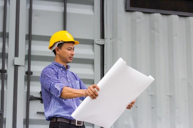 建設現場のコンテナーに近い紙の青写真プロジェクト計画を見てアジアのハンサムなエンジニア男。屋外で作業して、新しい建築プロジェクトの進捗状況を確認します。