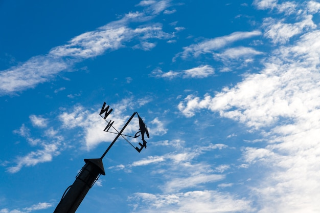 Сломанная флюгер с голубым небом с белым облаком.