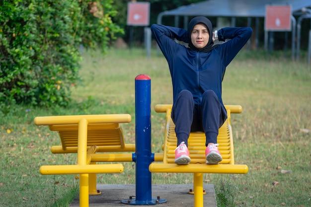 暗い服を着たイスラム教徒の女性とヒジャブは、公園で髪を練習します。