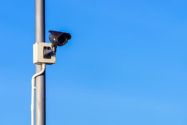 Черная камера видеонаблюдения на бронзовом металлическом шесте с белой пластиковой трубкой для проводов и ясного голубого неба