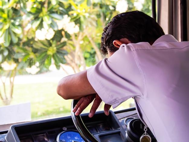 Водитель автобуса, одетый в белую рубашку, заснул на рулевом колесе автобуса