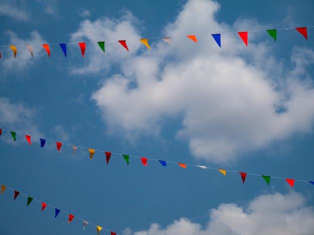 カーニバルフェアで雲の背景を持つ青い空にフラグのカラフルです