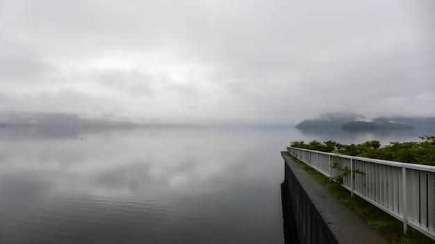 厚い霧と低い光の中で湖に白いフェンスとテラスのビュー。