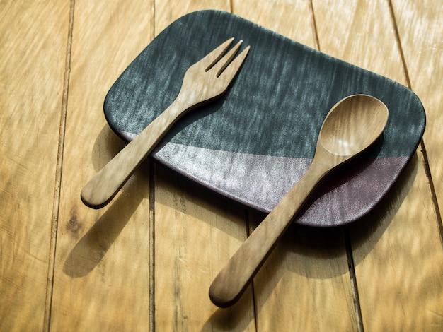 木のスプーンと朝の窓の近くの木製のテーブルの上の黒と茶色のプレートにフォーク