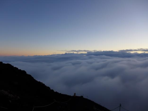 Голубое небо с облаками, глядя с вершины горы фудзи в японии на рассвете утром