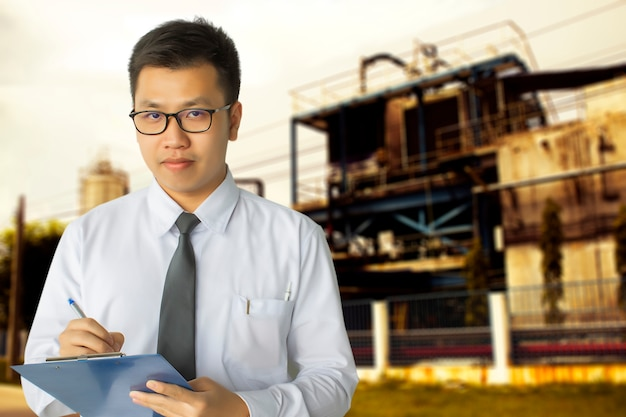 男性のエンジニアによる検査の工場でのメモ帳または業界でのメモ付き