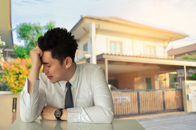 Азиатский бизнесмен грустный сидячий или проливной бизнес