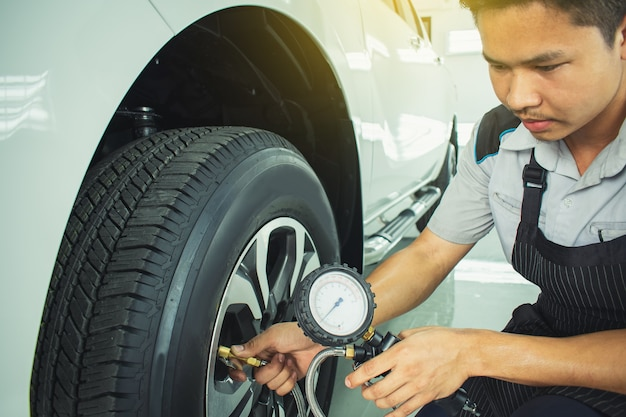Осмотр автомобиля азиатского человека измерение количества накачанных резиновых шин