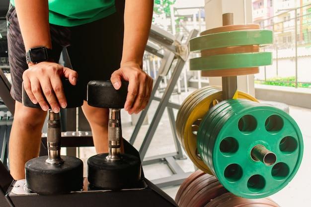 ダンベルの重みを持つアジア人ボディービルダーは、ハンサムな運動をします。