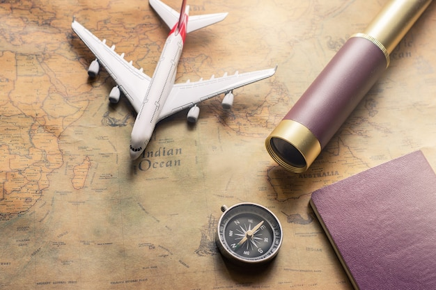 パスポート、双眼鏡、鉛筆、コンパス、旅行の冒険発見のための紙の地図上の飛行機とメモ用紙