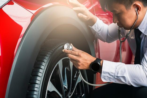 Азиатский человек держа стетоскоп с автошинами автомобиля резины осмотра.