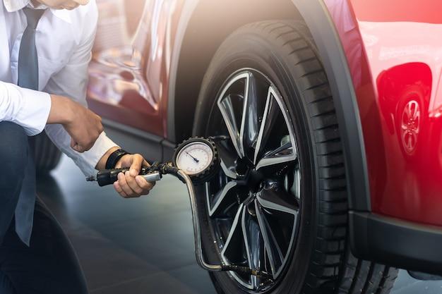 Осмотр автомобиля азиатского человека измерьте количество накачанных резиновых шин автомобиля. закройте ручную удерживающую машину. надутый манометр для измерения давления в шинах автомобиля для автомобиля, изображение автомобиля