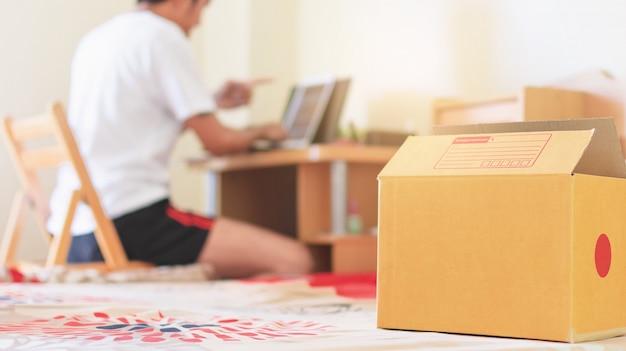 オンラインマーケティングを販売する男性の家の製品ボックスを閉じます。オンラインショッピングとオンライン販売の概念