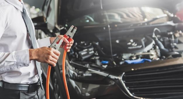 充電器のジャンパーケーブルを保持している人の検査産業からエンジンの修理のためのバッテリーサービスのメンテナンス。