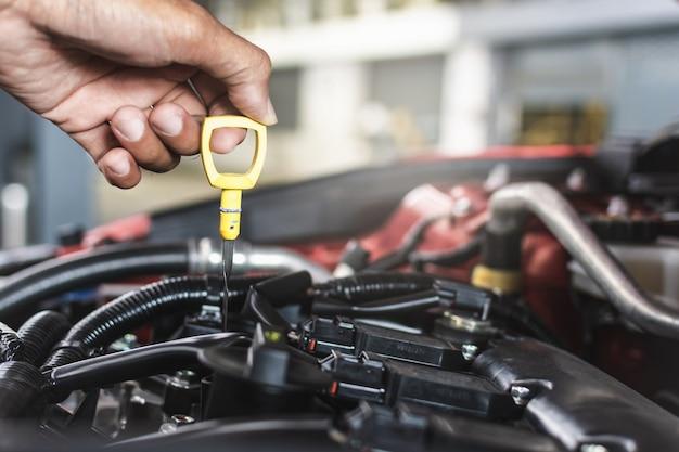 男サービスメカニックメンテナンス検査サービスメンテナンス車ガレージでエンジンオイルレベルの車をチェック