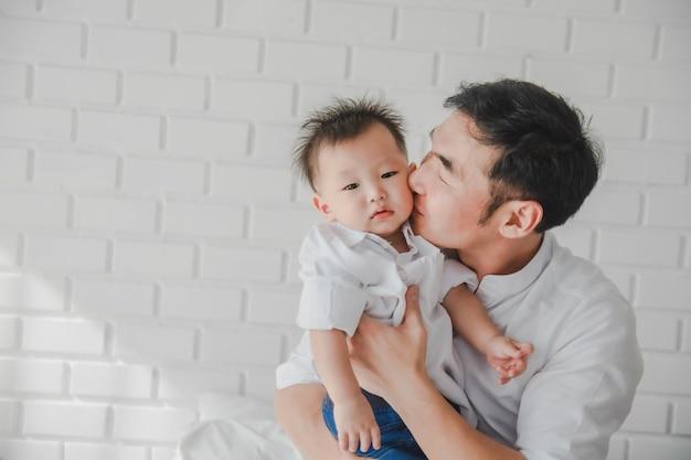 Азиатская японская семья отец поцелуй сына в белой рубашке с ребенком на руках