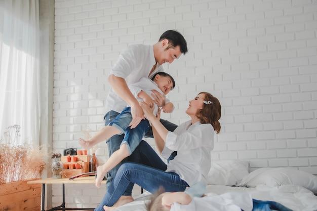Азиатский японский сын отца матери нося сын нося белой рубашки на спальне в белой комнате.